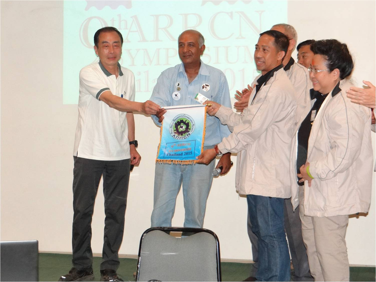 Satish Pande hands the ARRCN Symposium Flag to the team from Thailand. Photo by E. Nikolenko.
